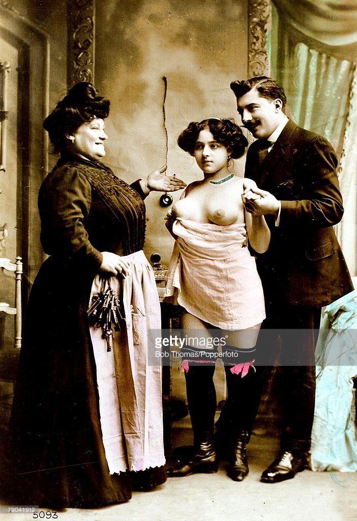 Postal erótica, Francia, años 1920s. Alcahueta o Madame con una prostituta joven y un hombre que va a entretenerse al burdel