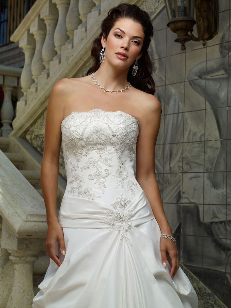 A true classic this strapless bodice crowned with a scalloped