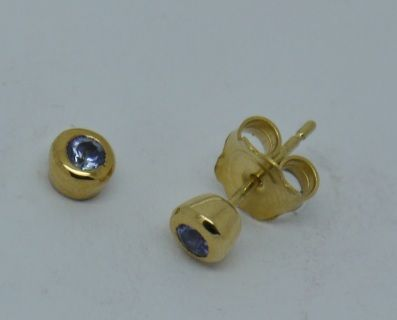 Pair of hand made 18ct yellow gold tanzanite ear studs. Each ear stud is set with one4mm round tanzanite in a rub over setting, with scroll fittings. Hand made in Keith Gordon workshop with London hallmarks. Supplied in a gift box.