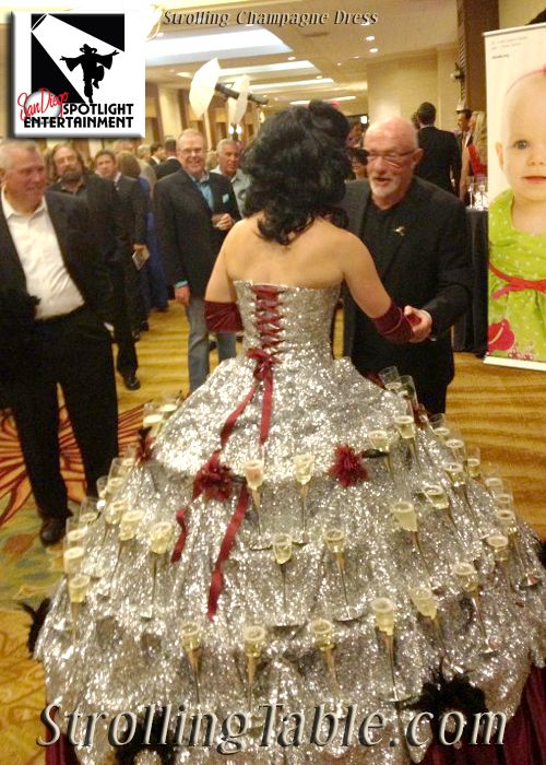 Strolling champagne dress - her skirt is holding glasses of champagne