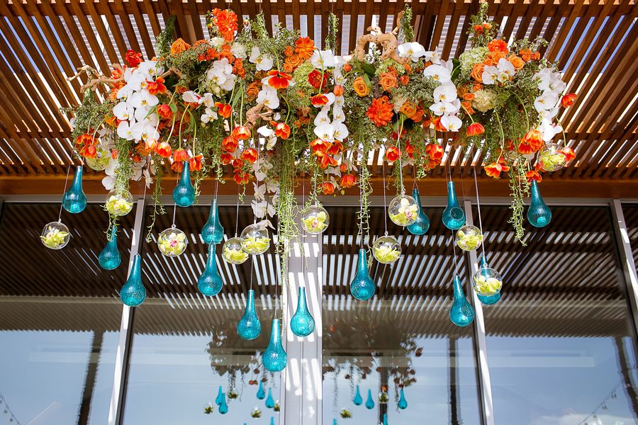 Tulips and colorful glass vessels create a dreamy floating flower effect as a key feature of the celebration. This presentation is natural, grand, and stunning. Photos: The Youngrens. Wedding Coordinator: Crown Weddings. Florals: Adorations Botanical Artistry.