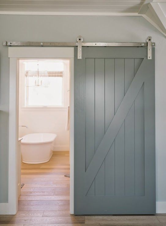 Gray Walls Frame A Gray Sliding Barn Door Which Opens To Reveal A Beautiful Bathroom Featuring A Frees Interior Barn Doors Barn Door Designs Bathroom Barn Door