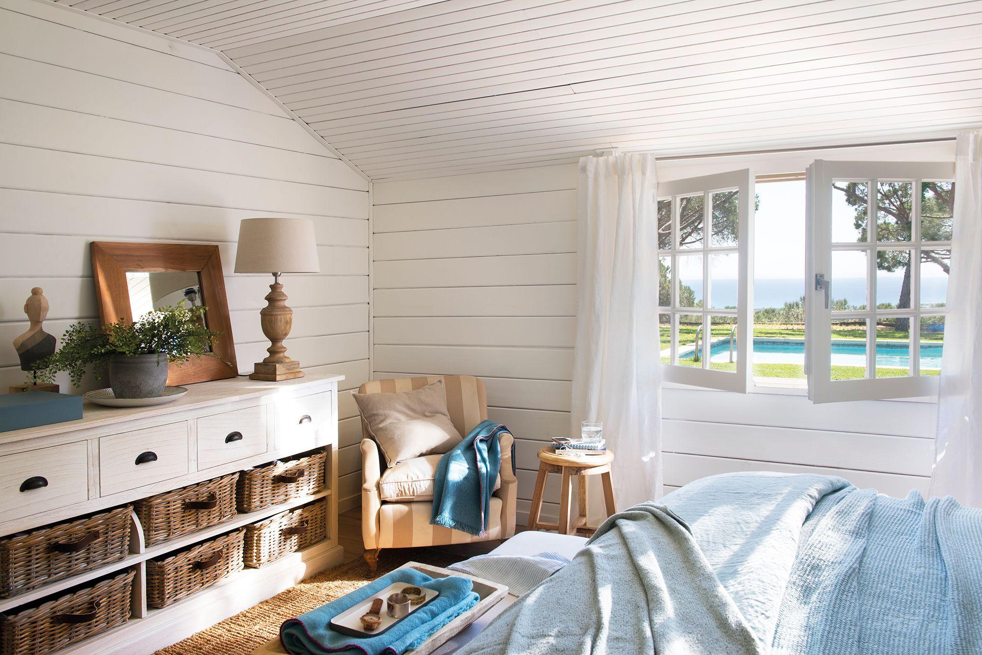 Dormitorio con paredes y suelo de listones de madera blanca y mueble ...