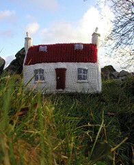 Looking out across a loch, surrounded by mountains is a little croft house with a red roof. This knitting pattern was inspired by that house which is located on the Applecross Peninsular, West Coast of Scotland. Make this knitted croft house as a child's toy or add extra weight and use as a bookend.