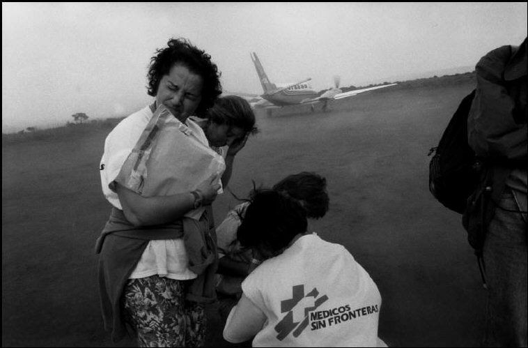 Eli Reed 1995. Workers from doctors without borders close their eyes against dust kicked up by a departing plane at the Benaco refugee camp in Tanzania.