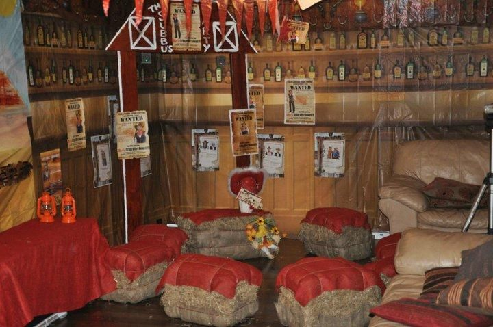Cowboy theme party decorating ideas with bales of hay and red covers