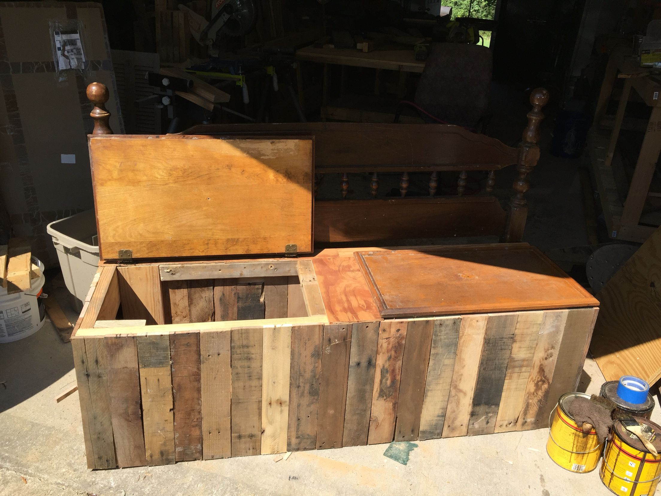 Pallet storage bench with reclaimed cabinet doors and headboard.