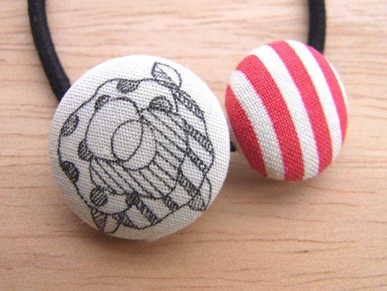 手描きのオリジナルくるみボタンと柄布地のくるみボタン2つで作った一点もののへアゴムです。イラストのくるみボタンは布地にひとつひとつ手描きしています。ヘアゴムと... ハンドメイド、手作り、手仕事品の通販・販売・購入ならCreema。
