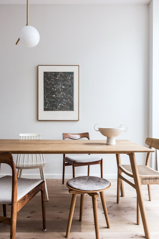 modern wood dining table with mismatched wood chairs. #woodtable #diningroom #diningtable #moderntable #mismatchedchairs #diningchairs #lighting #globelight #artwork #moderndiningroom #diningset