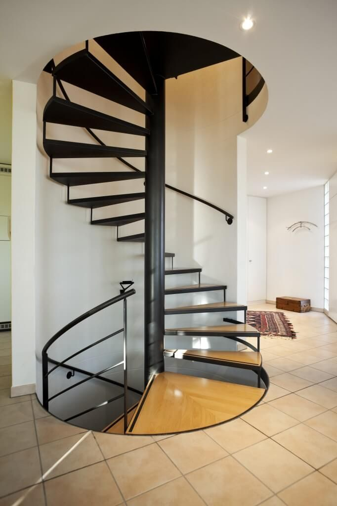 Spiral Staircase Encased In Semi Circular Stairwell Treads Supported By Thin Black Metal Open Stringers Steps Are Natural Light Wood