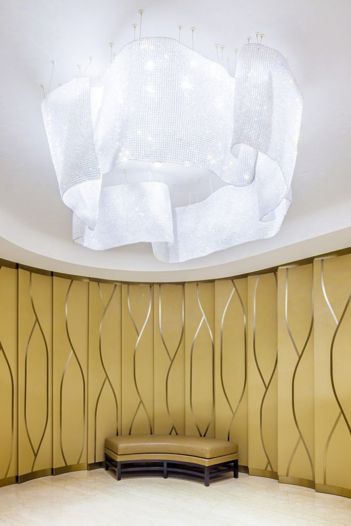 Glaze installation by Lasvit for JW Marriott Mumbai. Building on her well known Twill concept, Taťána Dvořáková designed a stunning lighting sculpture for the side lobby. Thousands of glittering fine crystal beads are woven into a fabric-like texture and folded with paper-like lightness. The design was inspired by a crack in the ceiling of an old building where water had frozen into delicate sheets resembling veils. #design #bespoke #installation #interiordesign #glass #art #light #lighting