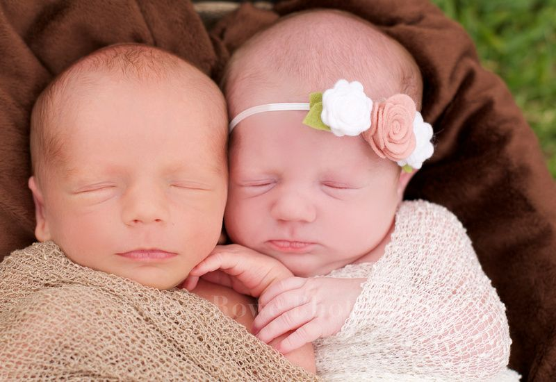 Newborn twins swaddled in a blanket snuggling together