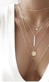Acumulación de finos collares de oro. Collar medallón, collar bar y collar …