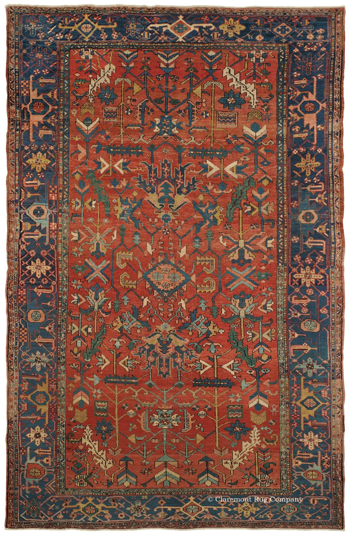 HERIZ, Northwest Persian 8ft 2in x 12ft 4in Late 19th Century  This extremely unique antique Persian Serapi Heriz carpet boasts a wondrously inventive all-over pattern composed of unabashedly idiosyncratic archetypal motifs, which are asymmetrically placed on an exuberant naturally dyed persimmon orange field. The composition is framed by a frequently striated, rich sapphire blue border. This folkloric 19th century carpet would have an equally striking effect on either a traditional or…