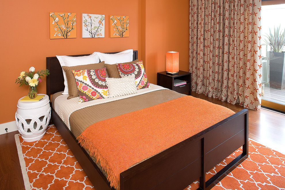 baroque quatrefoil bedding in bedroom contemporary with angled bed next to orange walls alongside garden stool