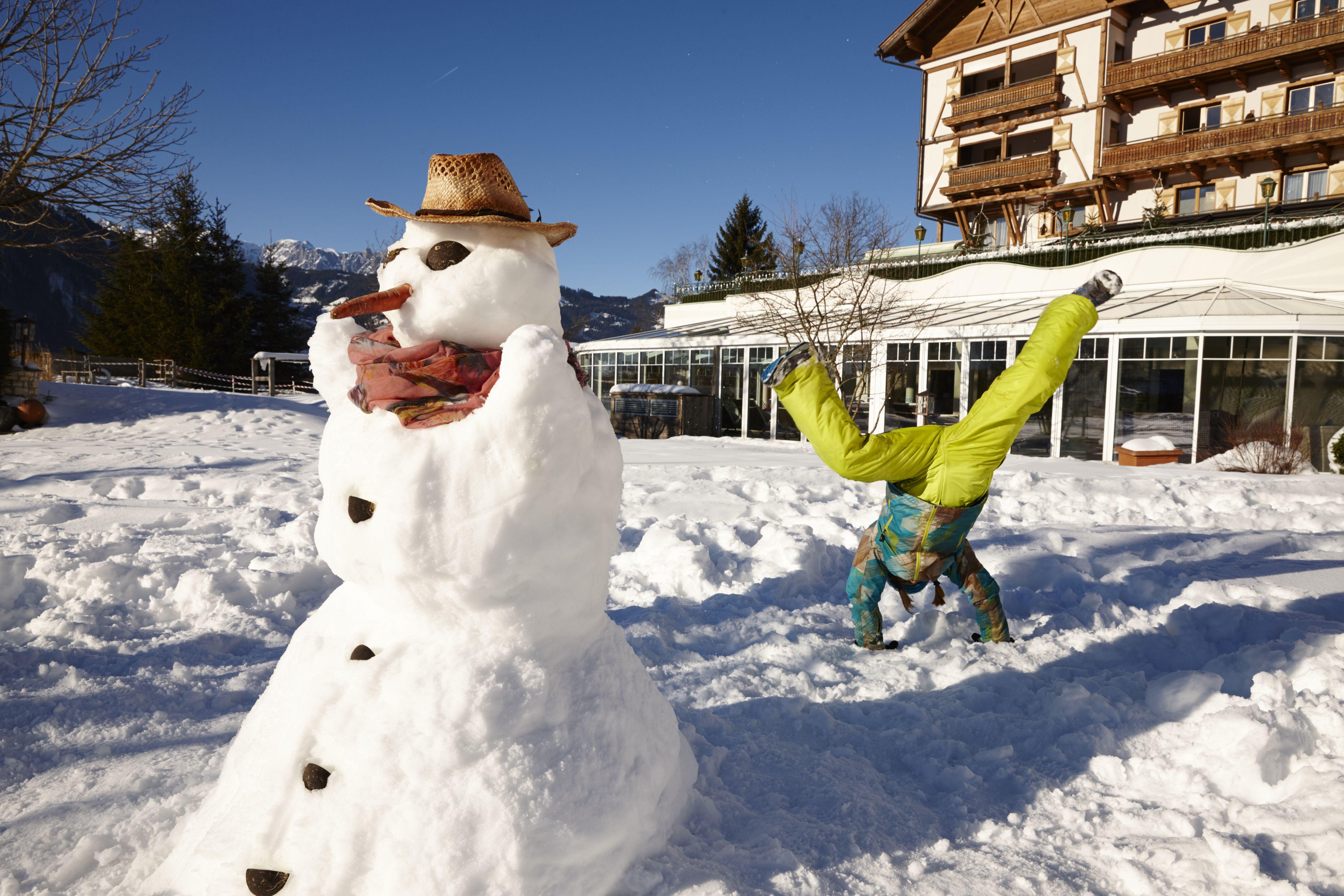 Schneemann bauen im Oberforsthof Garten. Das Familienhotel in Salzburg. Verbringen Sie Ihren Urlaub mit den Kindern in Österreich