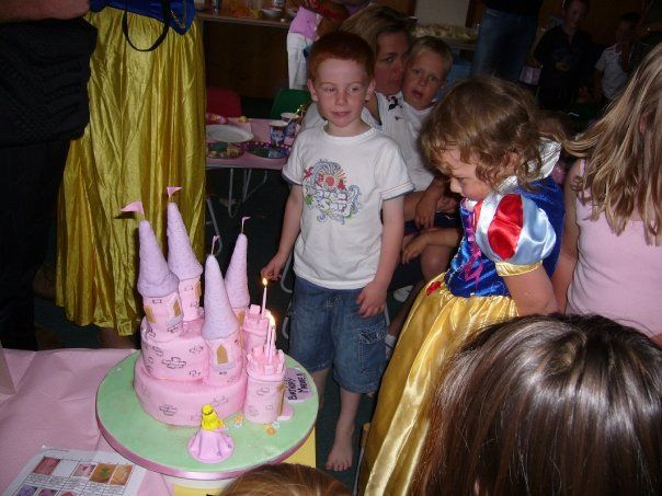 Pink Girls Castle Birthday Cake - This was for my daughter Maddie Simpsons 3rd Birthday. I wrapped purple icing round icecream cones and brought the figure which I still have. The cake is sloping and sliding and held up with many skewers! Green icing on the board makes a big difference.