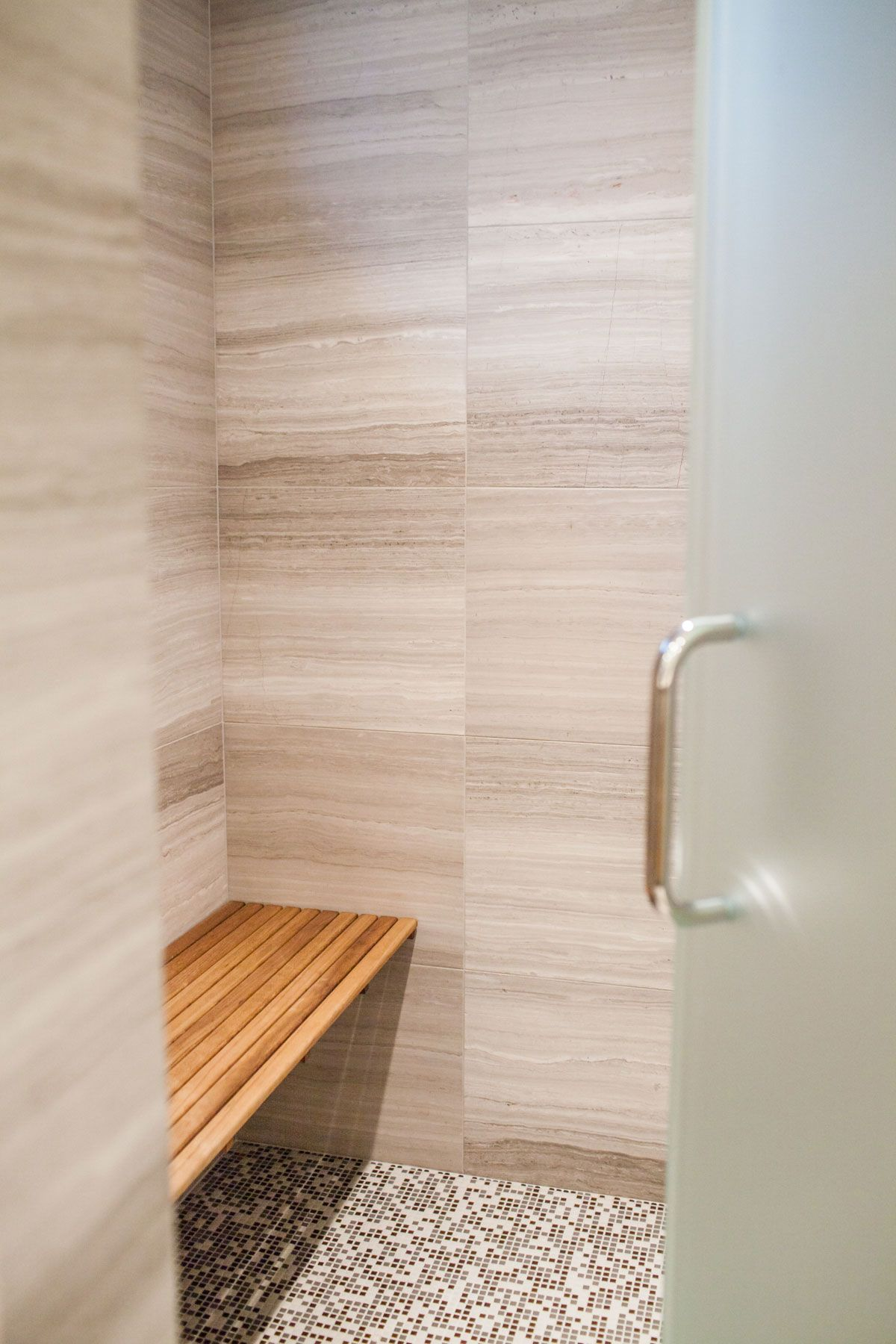 Shower room interior. Large stone tiles on the wall, mosaic tile ...