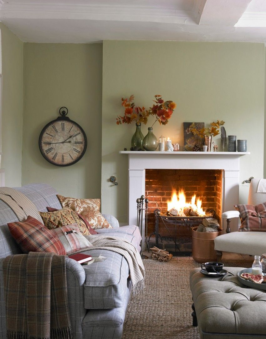 Cushions in a variety of autumnal prints and colours blankets and an open fire all create a warm and cosy welcoming feel in this country living room