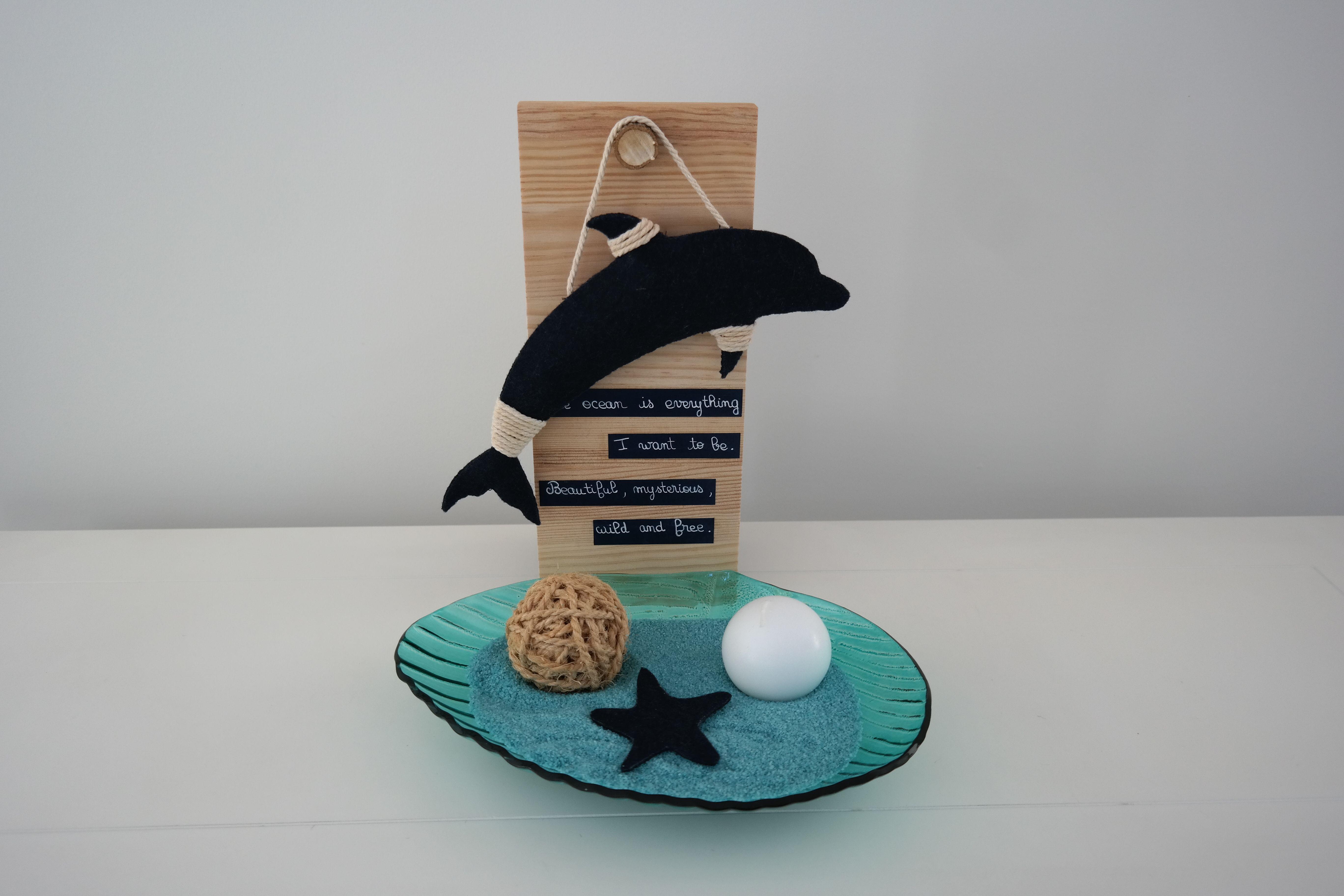 Peace Dolphin é uma decoração da ArteNatis constituída por:  - Uma peça em forma de golfinho, realizada à mão em feltro azul-escuro, pendurada num suporte em madeira (pinho natural).  - Uma peça em vidro colorido, em forma de concha, contendo pó decorativo, uma vela esférica branca, uma bola em corda de sisal e uma estrela-do-mar em feltro azul-escuro.