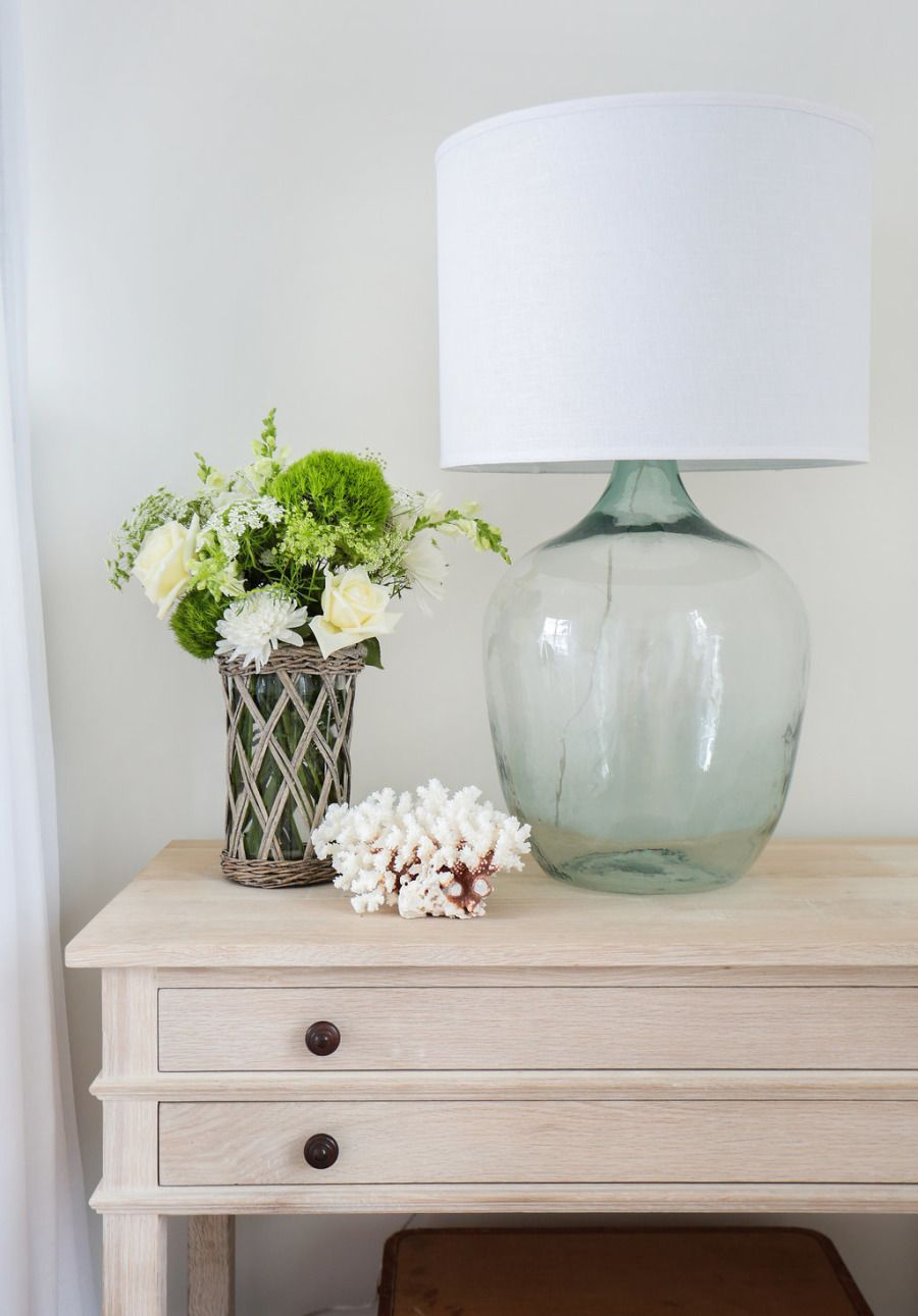 Creme nightstand, clear glass and white lamp, and flower decor