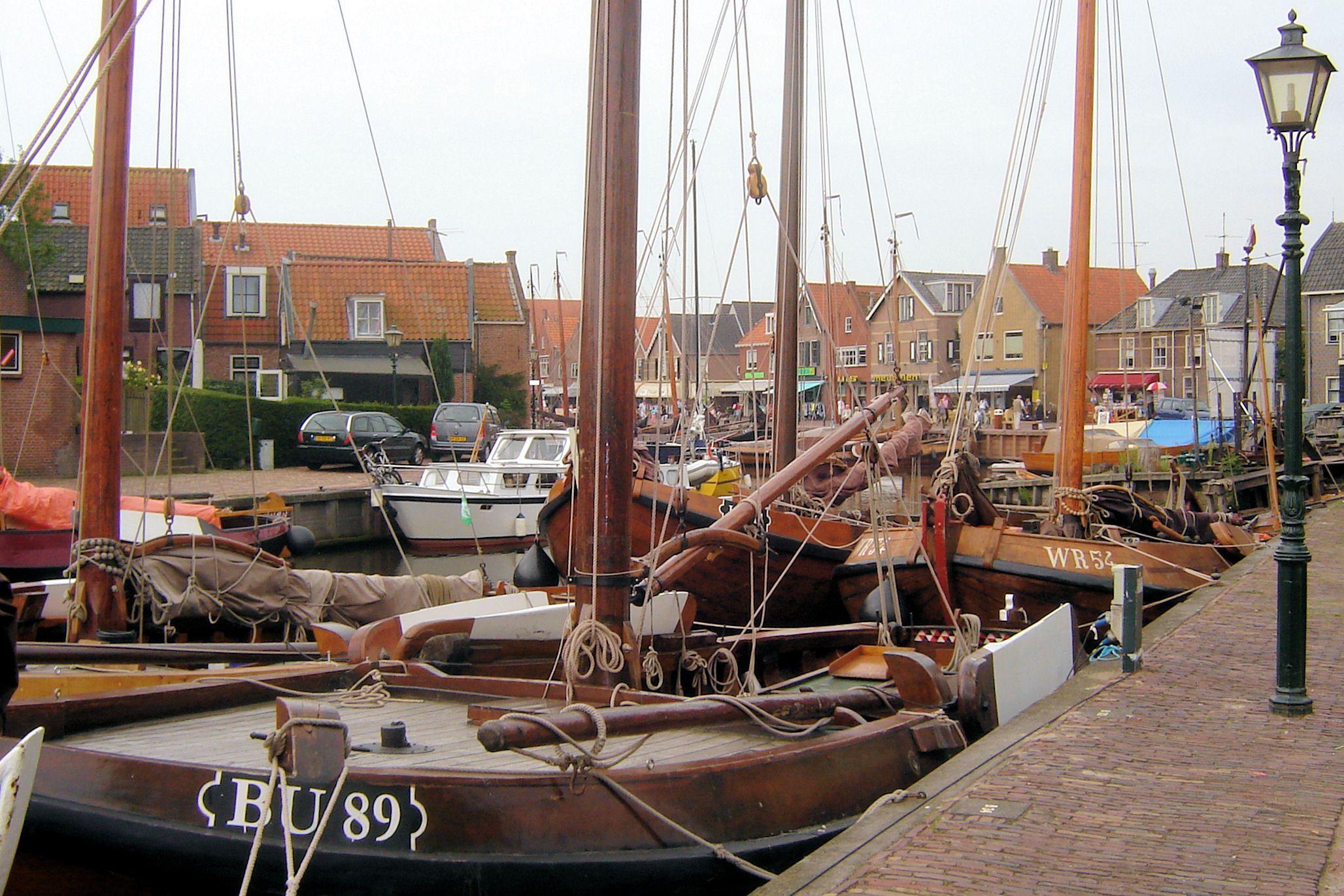 Voorbij het kantoor van de havenmeester heb je vanaf een bankje aan het water een prachtig uitzicht op het Eemmeer met de bruine zeilen van de botters.