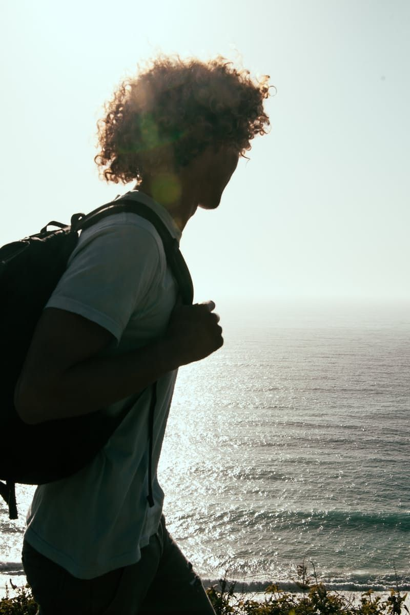 New free photo from Pexels: https://www.pexels.com/photo/man-in-white-t-shirt-carrying-backpack-looking-at-sea-during-daytime-27338/ #man #person #water