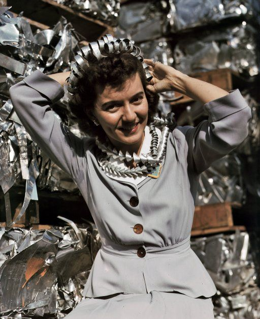 """October 1942. """"Office employee Annette del Sur publicizing salvage campaign in yard of Douglas Aircraft Company, Long Beach, California. The earrings and hair ornaments are fashioned from aluminum turnings.""""  4x5 Kodachrome transparency by Alfred Palmer for the Office of War Information."""