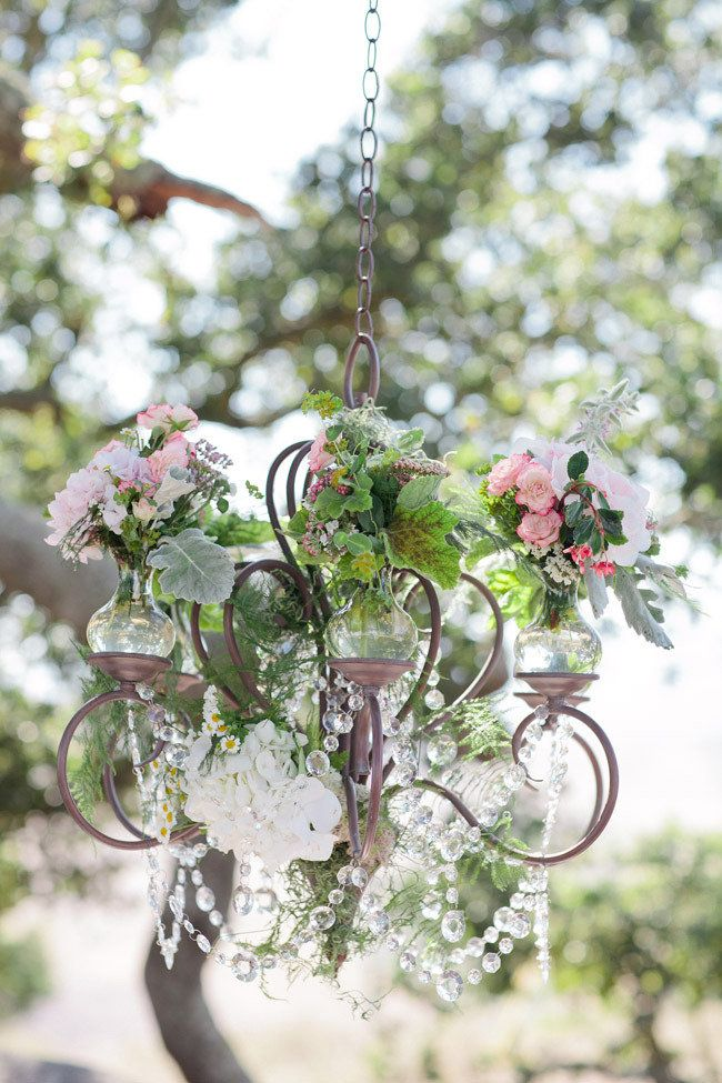 love the idea to hang chandeliers with flowers on them for an outside reception