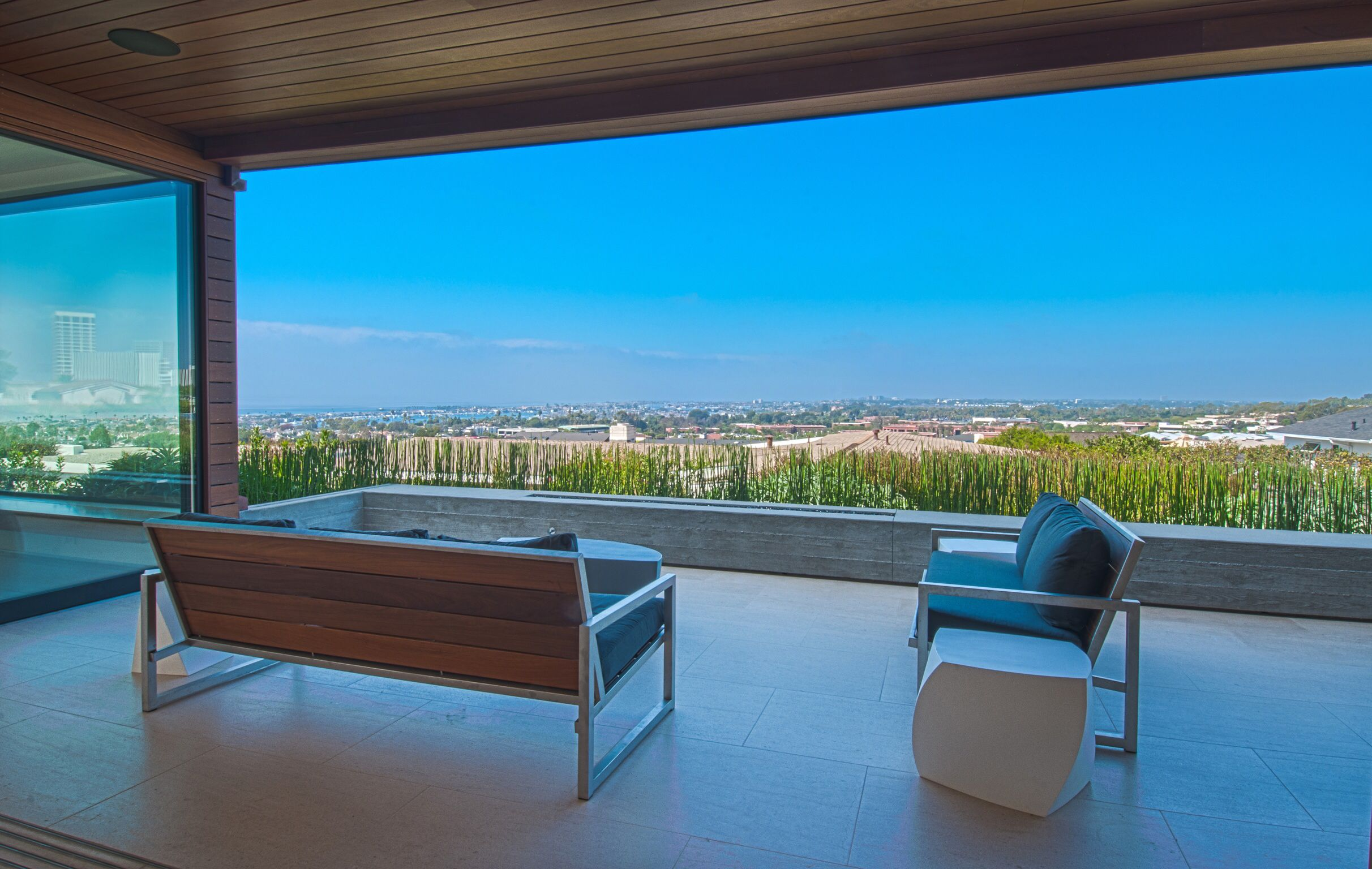 covered outdoor living room with a gorgeous bay ocean and