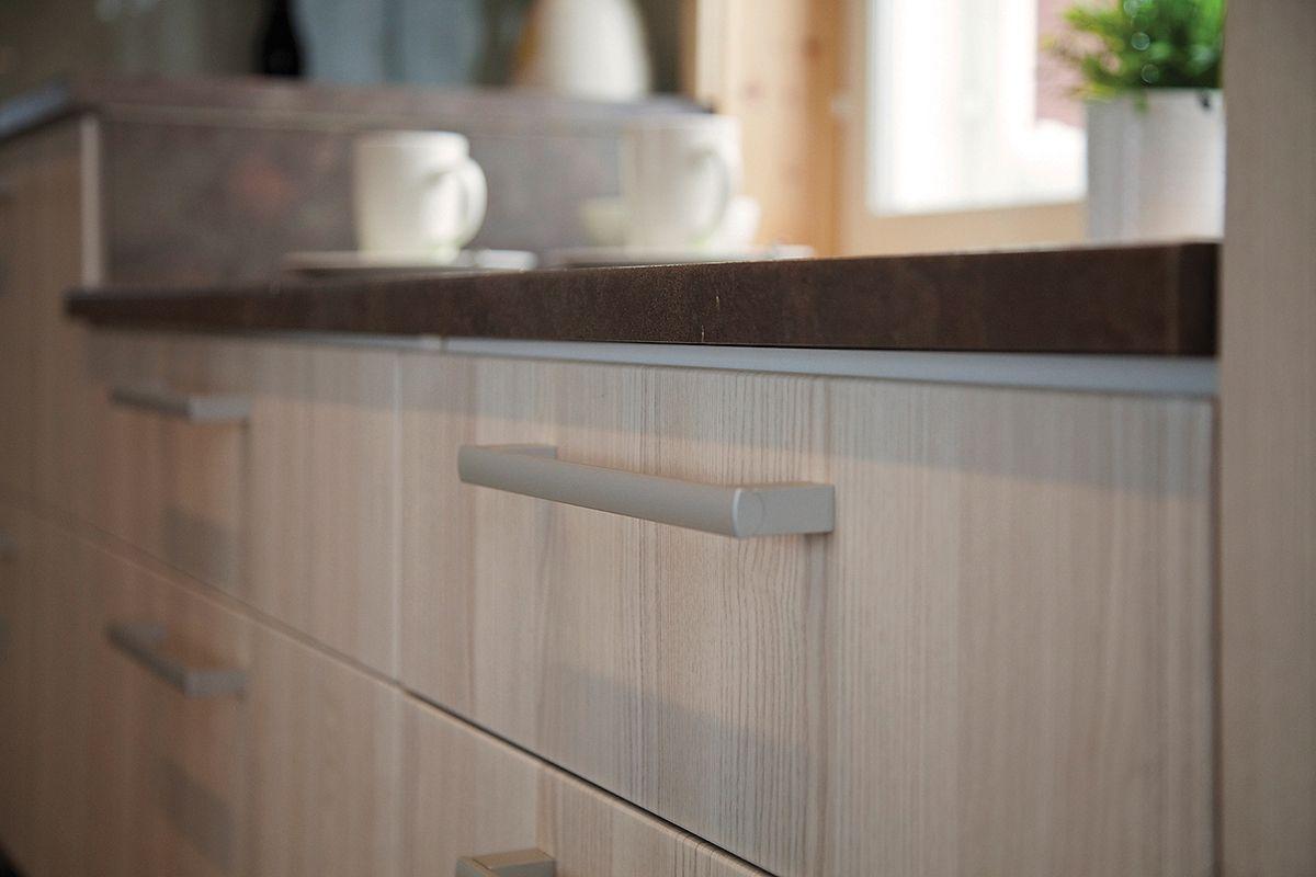Lämpimät sävyt pinnoissa luovat kotoisaa tunnelmaa. Kuvan kotoisassa keittiössä ovina: Simple, vaalea saarni sekä tasona: laava. www.toivekeittiot.fi