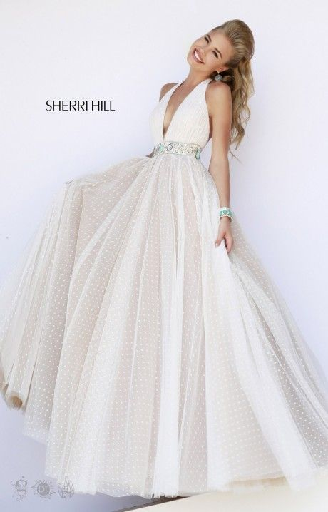How totally dreamy is Sherri Hill 11250? This ivory ballgown is the picture of perfection when it comes to looking like a serious fashionista! This design includes a deep V halter top with the ever stylish low open back with a flattering waistline. The top is made of the ruched tulle material with dainty polka dot print. The waistline is embellished with Sherri Hill's notorious style of glamorous beading, and these rhinestones, gems, and sequins stand out like no other! The flowy ballgown…