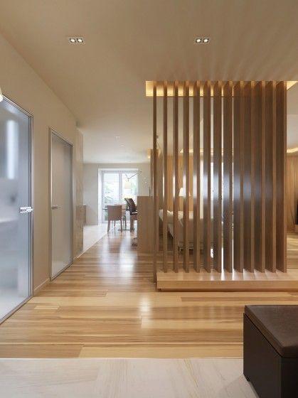Separador de ambientes con listones de madera con un punto de luz en