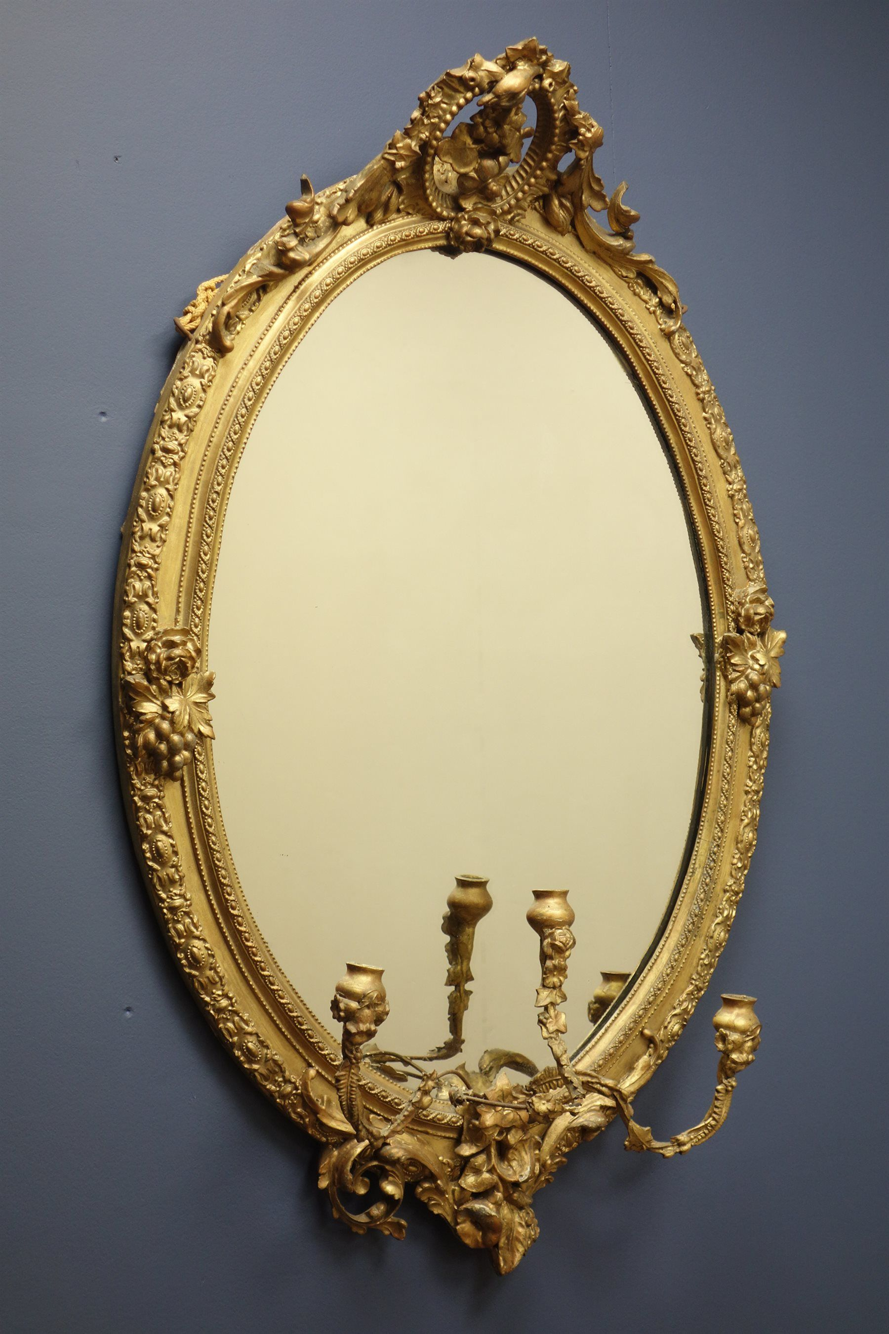19th century gilt wood and gesso oval mirror, with candle sconces ...