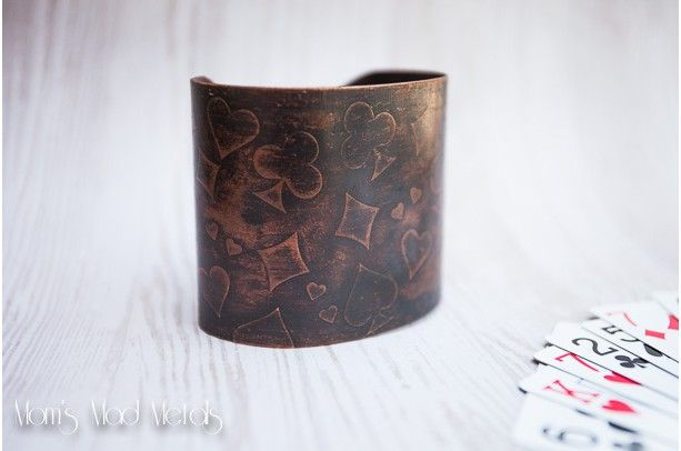 This is a 2 inch wide and 6 inches long copper cuff that is etched with a playing cards theme. It has been allowed to develop a nice brown patina that is accomplished through heat.