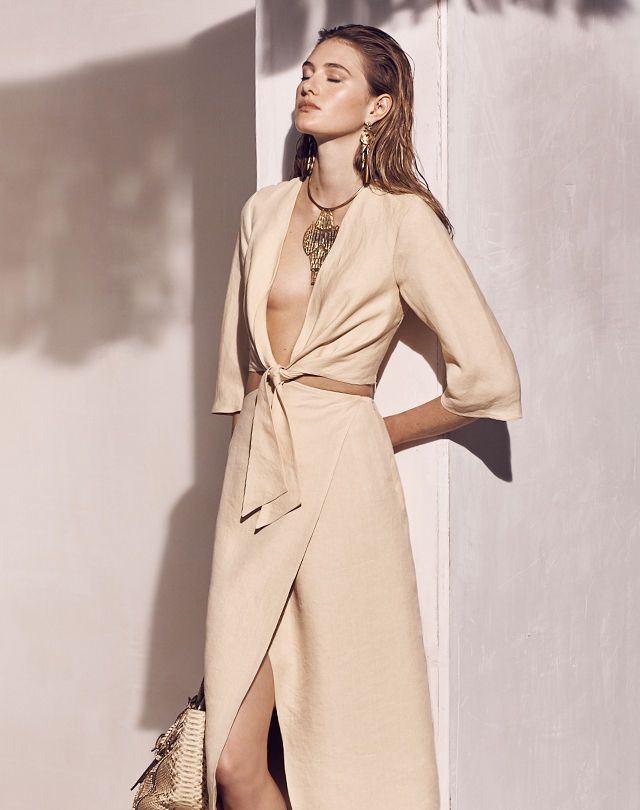 Woman in utility-inspired wrap dress leans against wall