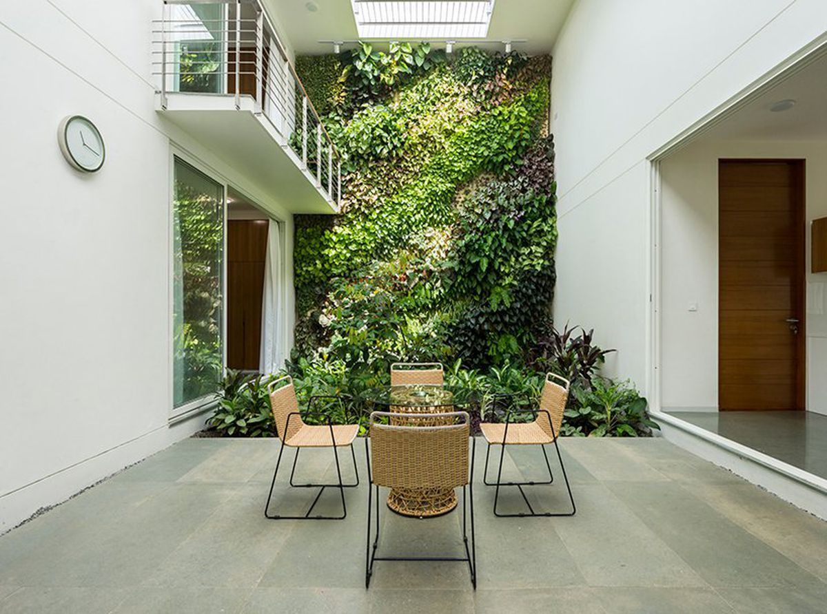 Indoor-outdoor modern house is immersed in greenery | Kerala house design, Tropical house design, Courtyard design