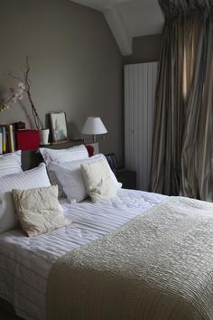 Chambre Beige grisée avec une multitude de coussins et une pointe de ...