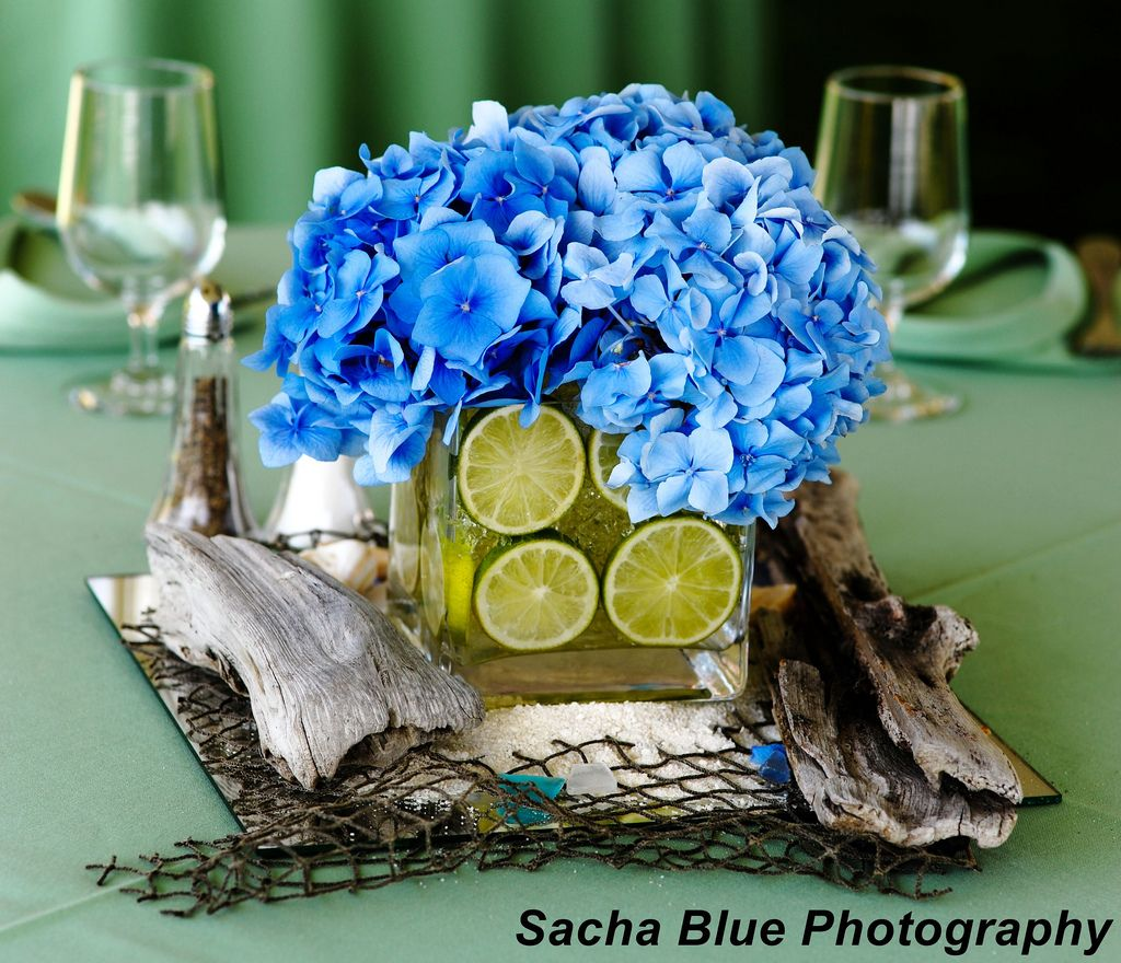 Hydrangea centerpiece with cut limes in a cube vase.