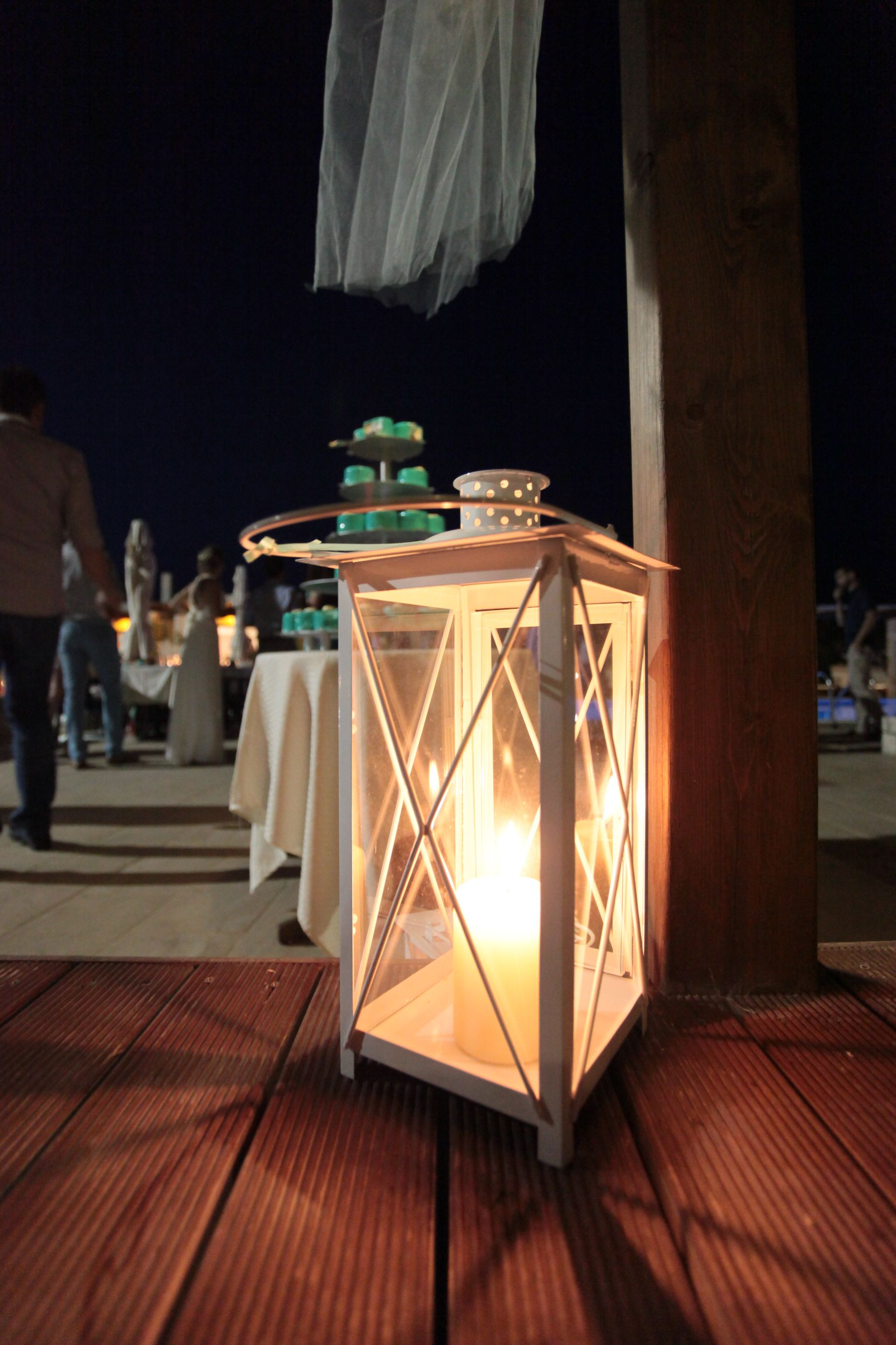 White candle lanterns. Imagine this with starfish inside and our ribbon of our colour.
