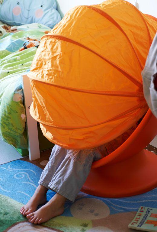 Isaac sa skrýva v sýto oranžovom kresle v novej spálni.