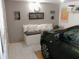 """Garaje convertido en la """"Habitación"""" del coche. Con tarima flotante un banco de dM y unos cojines, la llegada a casa se hace más cálida y hogareña."""