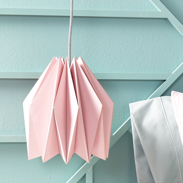 Swapping your lamp with a hanging pendant light is a bright way to update your room. Skip the lighting aisle at the hardware store and instead make your own affordable pendant with our modern paper lampshade. This project involves folding paper into a gorgeous geometric shape that sits over a pendant cord kit. Follow our instructions below to learn how to make your own origami-inspired paper lampshade. #papercrafts #hangingpendant #origami #bhg