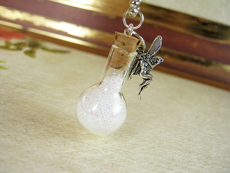 """Small round-bottom vial filled with """"fairy dust"""" with silver fairy charm.  Available in 19 colours.  Bottle measures approx 1.25"""" in height and comes on 18"""" silver ball-chain.  Bottle cork will be secured in place with waterproof sealant to prevent leakage and/or cork damage. All contents a..."""