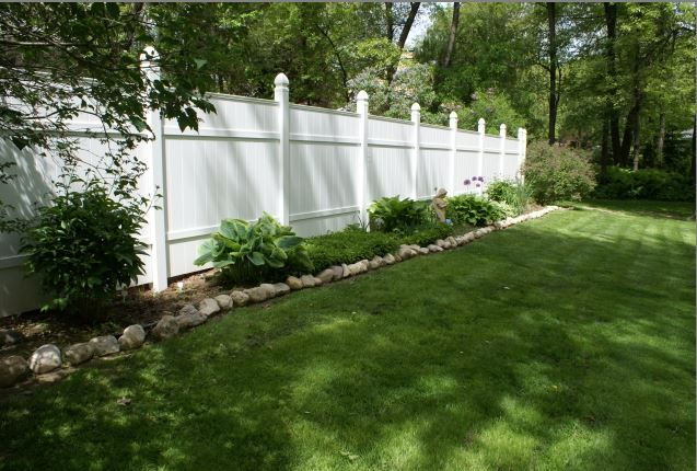 white backyard fence with landscaping