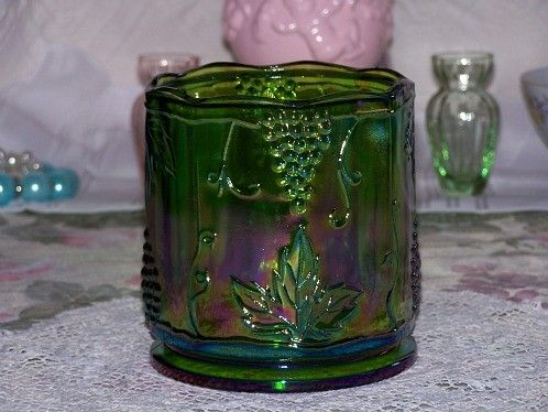 Vintage Green Carnival Glass Jar Canister Indiana Glass Company. Measures about 5 inches tall, and 4-5/8 inch wide. No lid with this. Very Good Condition, clean, shine, almost like new. Indiana Glass originally made this a 3 piece canister set with a grape design of green iridescent carnival glass. The canister jar has the grape and leaf design, and is sometimes called Harvest Grape. This is a heavy, and solid piece with a beautiful iridescent coloring of green, purple, blue, and a very…