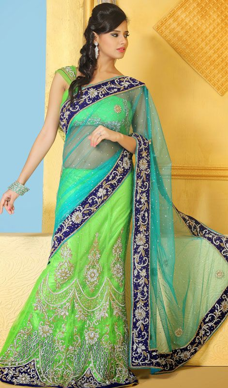Designer cyan blue and lime green embroidered net lehenga sari has gold and silver mixed embroidery. Sari is decorated with all over contrast blue border with foliage pattern. Lehenga part is decorated with glass beads, pearls, foliage motifs and crystal stones and that of other second cyan blue palav is with scattered stones and motifs. Sari comes with matching stitched blouse as shown in the picture. #BeautifulLehengaSarees #PartyWearLehengaSarees