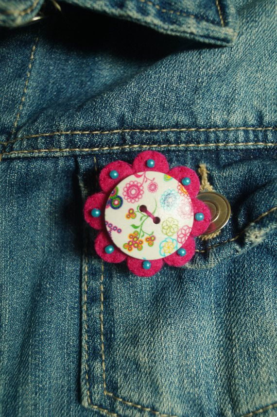 A cute handmade button brooch with a pink felt backing, decorated with beads.