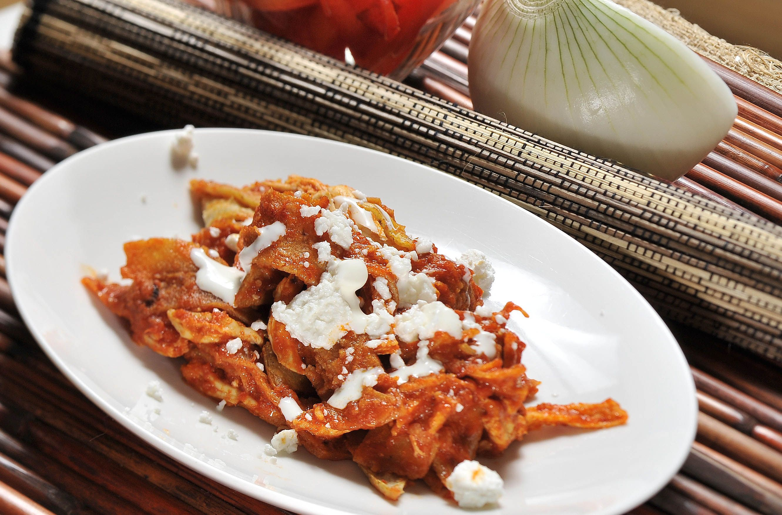 1 clove of garlic 2 pieces of chile guajillo 2 pieces of tomato 12 pieces of corn tortilla Canola oil salt 1/4 piece of white onion 100 grams of fresh cheese 1 cup shredded cooked chicken 1/2 cup cream of cow's milk 1 piece of chile de arbol