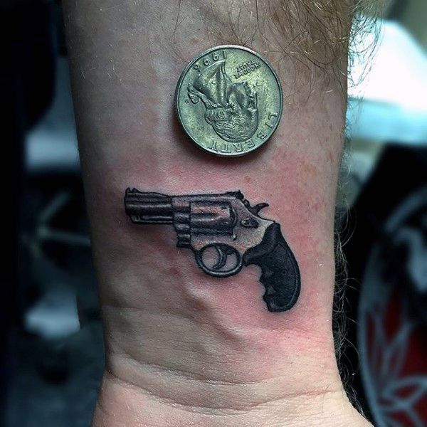 Guy With Small Pistol And 3D Coin Tattoo On Wrist ...